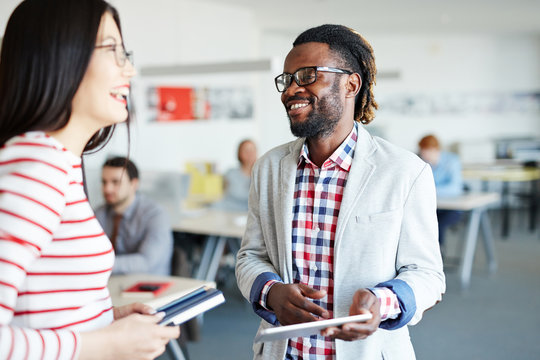 Male and female colleagues standing in open plan office and laughing at something, Afro-American employee holding digital tablet in hands