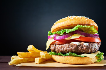 Craft beef burger and french fries on wooden table isolated on dark blue background.