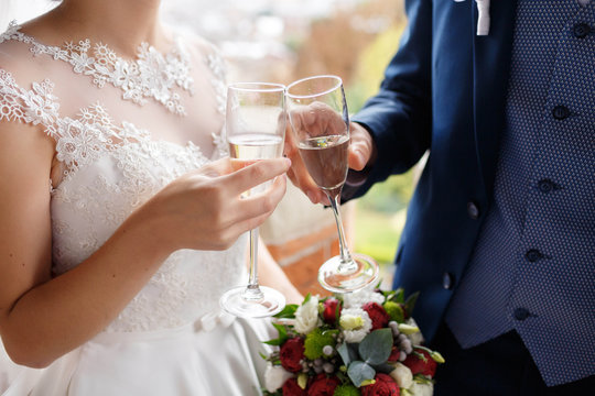 bride and groom holding glasses with champagne and clink