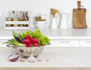 Fresh vegetables on wooden table over blurred kitchen counter interior