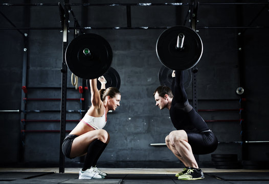 Motivational wide shot of young man and woman holding huge heavy barbells overhead looking at each other