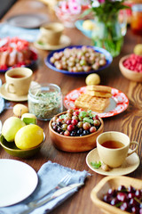 Breakfast table setting full of gooseberries and currant, fruits, freshly baked waffles and cups of scented tea