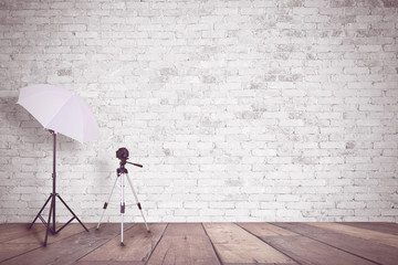 White brick wall in a photo studio. An umbrella for illumination and a tripod for a camera. Empty copy space for Editor's content.