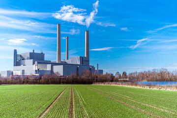 Heizkraftwerk neben einer Solaranlage und einem grünen Acker