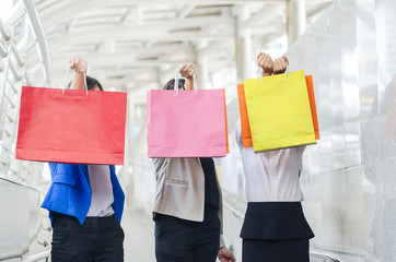 Group of shopping asia women holding up shopping bags.