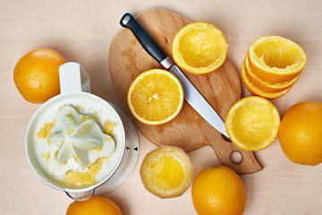 Juicer, knife and oranges on cutting board