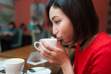 Asian Woman drink a cup of tea or coffee in cafe