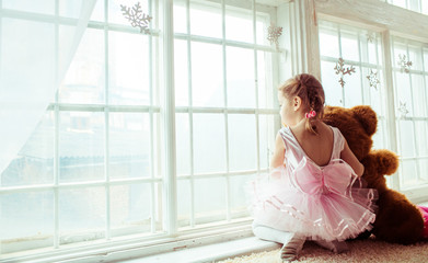 Little girl in pink dress sits with toy bear before panoramic window