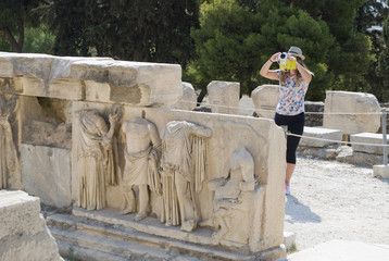 Young woman taking a photo of  an Acropolis