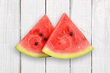 Two watermelon slices on white wooden background