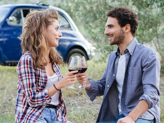 Couple of young lovers drinking red wine from glass goblet at picnic in countryside, Tuscany, Italy. Sitting on lawn among the olive trees on a late summer day, behind them  old blue car