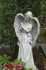 betende engelsfigur steht auf einem grab