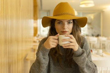Portrait of woman wearing hat and drinking coffee