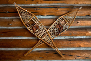 Pair of snow shoes hanging on a wooden wall