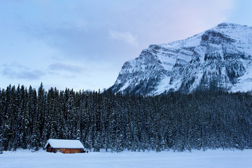 Cabin in the snow by forest and mountain