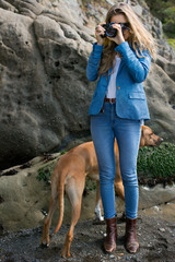 Woman taking photo with camera and dog