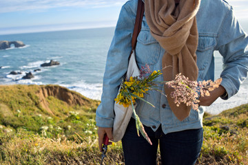 Woman holding flowers by coast