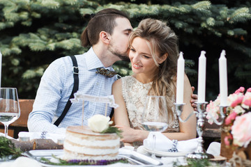 Bride and groom sitting on bench in park, holding hands of each other and bouquet. Groom holding his head on bride's shoulder and bride smiling broadly. Outdoor, full body
