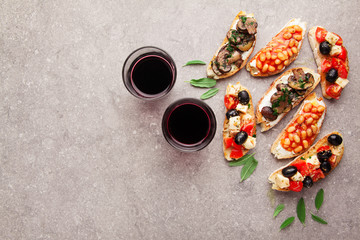 Brushetta set for wine. Variety of small sandwiches with caprese salad , white beans on the grill with tomato sauce and fried mushrooms with soft cheese, served with red wine on white
