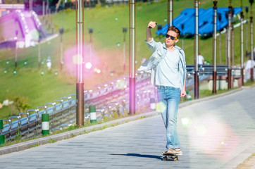 Boy teenager in sunglasses and jeans riding a skateboard and makes selfie on river embankment
