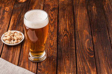 glass of light cold frothy beer, nuts old wooden table