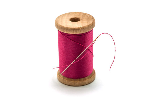 Isolated wooden spool of pink thread with a needle