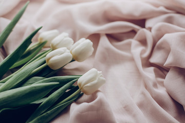 instagram spring photo. stylish white tulips on beige soft fabric on rustic table background. soft light, tenderness atmospheric moment. space for text. rustic wedding