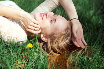 Blue-eyed Blonde Lying on the Grass with Dandelions. Cute Young Girfriend Lovely Laughing in Warm Sunny Day