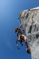 Young girl climbing on vertical wall with ropes outdoors warm summer day with clear blue sky.