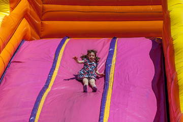 Young happy girl child in dress riding inflatable slide outdoors a warm summer day.