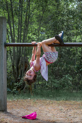 Cute girl in dress and shorts hanging up side down at a climbing frame outdoors, summer activity.