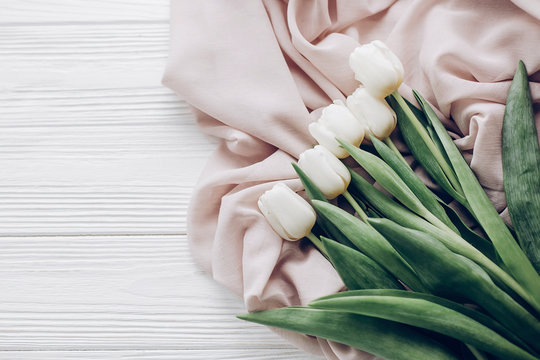 stylish white tulips on beige soft fabric and rustic wooden table background top view. hello spring flat lay. soft light, tenderness atmospheric moment. space for text. modern image