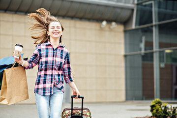 Happy hipster woman in plaid shirt running with disposable cups, suitcase and paperbag. Freedom Travel and Holiday Concept.