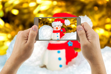 Man using mobile phone taking picture of snowman with blurred background. Celebrating  Christmas & New year festival.