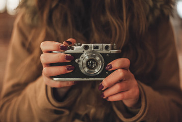 Hipster girl with retro camera taking photos outdoors