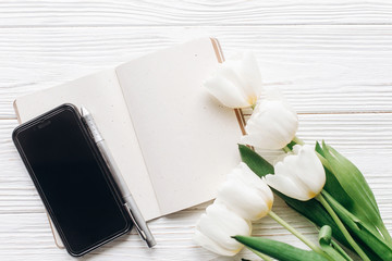 phone screen and notebook pen and stylish tulips on white wooden rustic background. flat lay with flowers and paper note with space for text. woman working. idea book