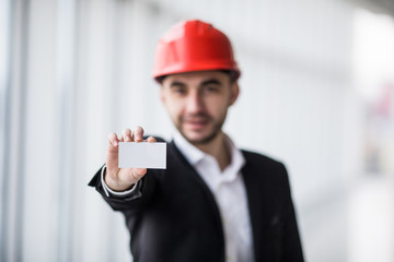 Construction worker holding blank business card in building construction.