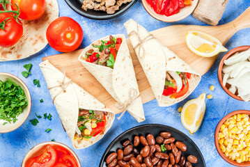 Street fast Mexican food, freshly prepared, homemade sandwiches burrito with beans, beef, corn, peppers, tomatoes and herbs. On the blue background of the concrete stone, copy space