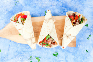 Street fast Mexican food, freshly prepared, homemade sandwiches burrito with beans, beef, corn, peppers, tomatoes and herbs. On the blue background of the concrete stone, top view copy space