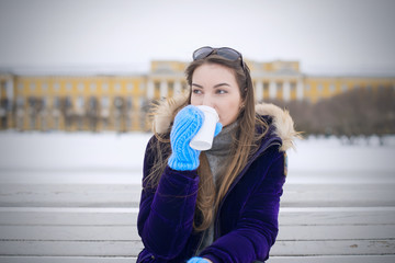 A beautiful girl from Europe sitting on a white bench in the Champ de Mars in St. Petersburg, Russia city in a purple jacket. She drinks coffee from a white cup.
