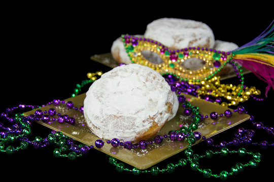 paczki with Mardi Gras beads and mask on gold plate