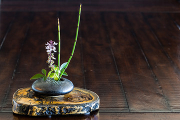Ikebana flower arrangement on the wood.