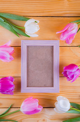 Bouquet of tender pink tulips with empty photo frame on light wooden background