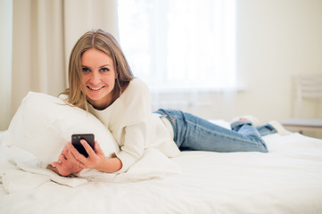 Beautiful woman sending a text with a mobile phone in bed