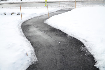 winding sidewalk after snow with snow removed