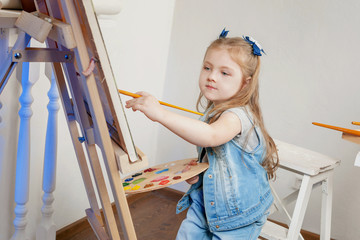 Girl artist paints on an easel paints