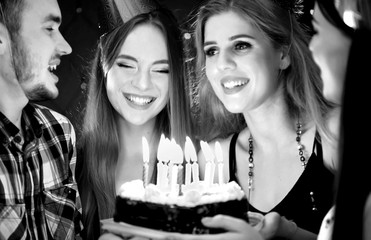 Black white pictures of happy friends birthday wear in hat party with candle celebration cakes. People looking at burning candles. Two women and man have fun.
