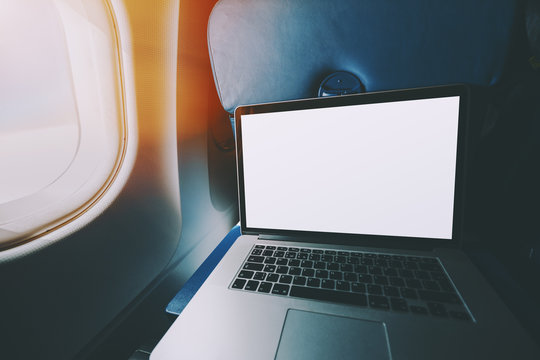 Wide angle shoot of modern laptop with blank screen on the blue table of airplane seat, mock up of portable computer next to porthole of flying plane with sunny day outside