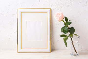 Gold decorated frame mockup with tender pink rose in glass