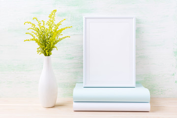 White frame mockup with ornamental green grass and books